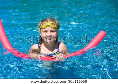Adorable little girl swimming with a pink foam noodle in a pool  - stock photo