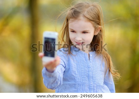 Adorable little girl taking a photo of herself on beautiful summer day - stock photo