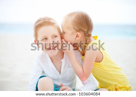 Adorable little girl telling secret to her brother - stock photo