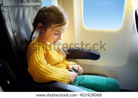 Adorable little girl traveling by an airplane. Child sitting by aircraft window and looking outside. - stock photo