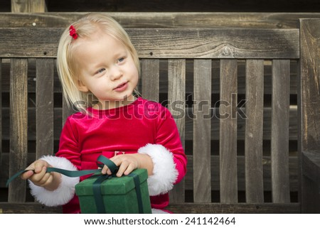Adorable Little Girl Unwrapping Her Gift on a Bench Outside. - stock photo