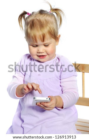 Adorable little girl using mobile phone on white background