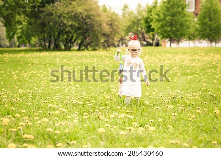 Adorable little girl walking on the dandelion field. White dress with light brown bow. Red ribbon on her head. Colorful umbrella in her hand. Big funny glasses on her face. Toned image. Vintage style. - stock photo