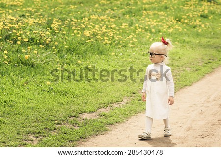 Adorable little girl walking on the dandelion field. White dress with light brown bow. Red ribbon on her head. Big funny glasses on her face. Toned image. Vintage style. - stock photo