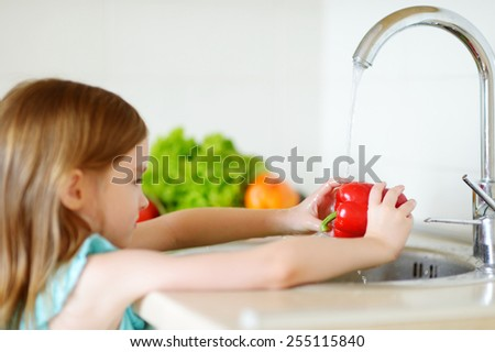 Adorable little girl washing vegetables in a kitchen - stock photo