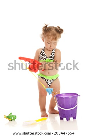 Adorable little girl wearing a bikini and playing with a pail of water and a fishing pole.  Isolated on white. - stock photo