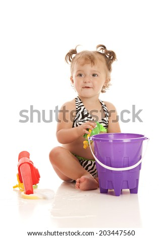 Adorable little girl wearing a bikini and playing with a pail of water and toy fish.  Isolated on white. - stock photo
