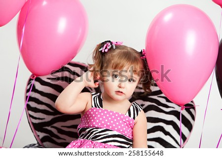 Adorable little girl wearing a pink and zebra print dress surrounded by pink and black helium filled balloons. - stock photo