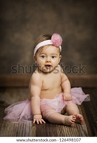Adorable little girl wearing a pink tutu and headband.