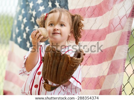 Adorable little girl wearing a vintage baseball uniform and baseball mitt and standing in front of an American Flag hung from a chain link fence.   - stock photo