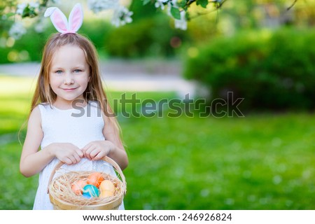 Adorable little girl wearing bunny ears holding a basket with Easter eggs in a blooming garden on spring day - stock photo