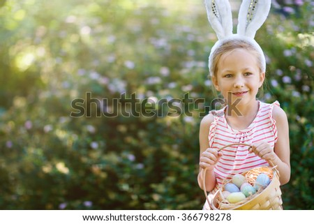Adorable little girl wearing bunny ears holding a basket with Easter eggs outdoors on spring day - stock photo
