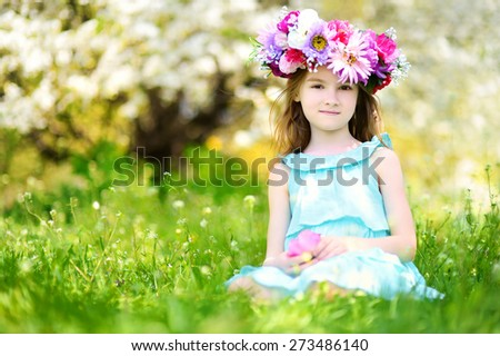 Adorable little girl wearing flower crown sitting in blooming cherry garden on beautiful spring day - stock photo