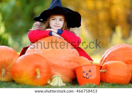 Adorable little girl wearing halloween costume having fun on a pumpkin patch on beautiful autumn day