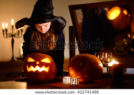 Adorable little girl wearing Halloween costume having fun with carved pumpkin in dark room on Halloween