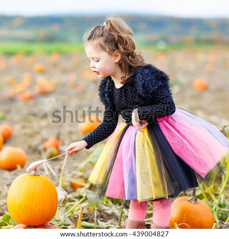Adorable little girl wearing halloween fairy costume having fun on a pumpkin patch. Traditional family festival with children. Happy child playing