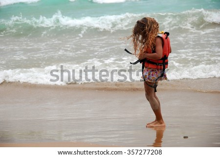 Adorable little girl wearing orange life jacket on the beach  Female child with long blonde hair dressing up her life saver vest in front of big ocean waves on a sunny day in tropical summer climate - stock photo