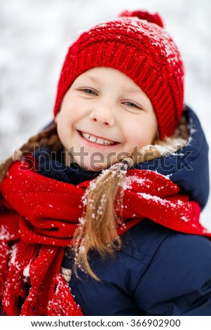 Adorable little girl wearing warm clothes outdoors on beautiful winter snow day