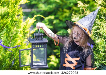 Adorable little girl wearing witch costume casting a spell on Halloween. Trick or treat. - stock photo