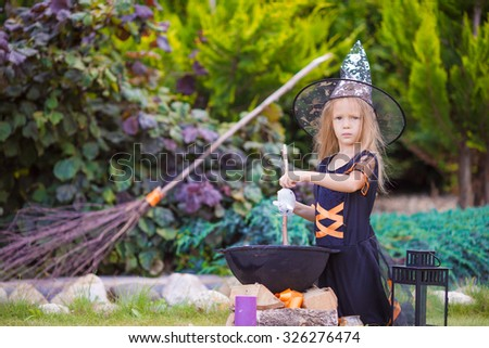 Adorable little girl wearing witch costume with broom on Halloween - stock photo