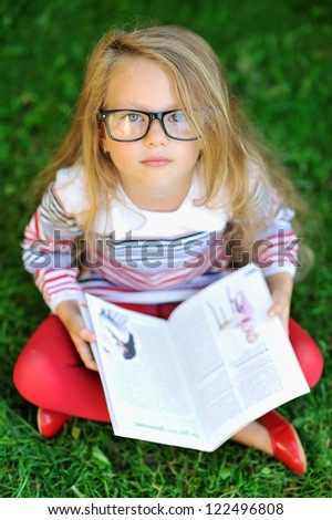 Adorable little girl with a book - stock photo