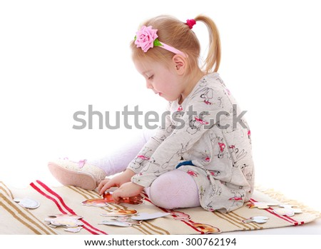 Adorable little girl with a ponytail on her head in a long cotton dress sits on the Mat in a Montessori kindergarten . The girl goes through the hands of the card-Isolated on white background - stock photo