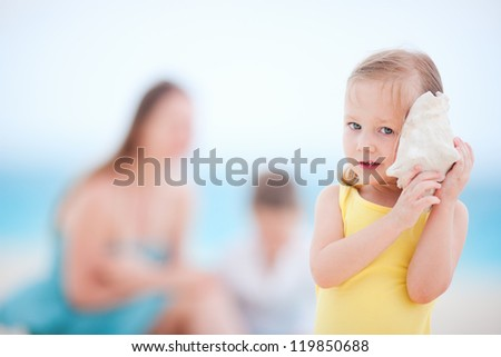 Adorable little girl with a seashell at the beach