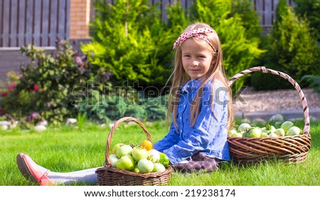Adorable little girl with autumn harvest of tomato on the lawn