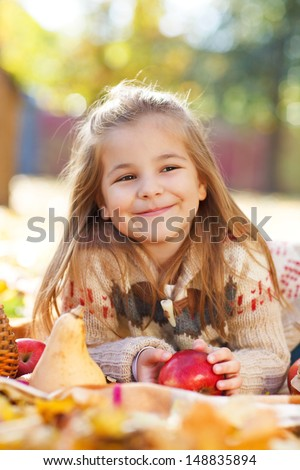 Adorable little girl with autumn leaves and apple in the beauty park - stock photo