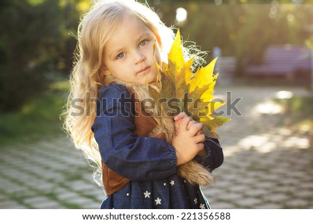 Adorable little girl with autumn leaves in park - stock photo