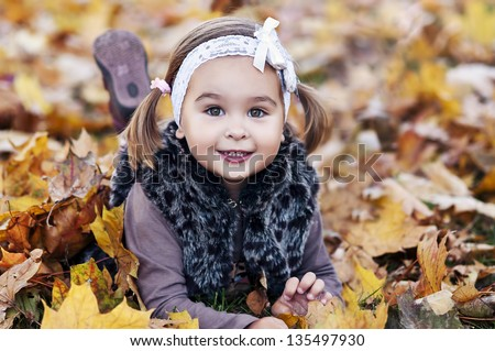 adorable little girl with autumn leaves in the beauty park - stock photo