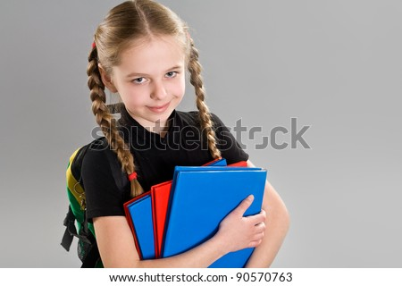 Adorable little girl with backpack and books - stock photo