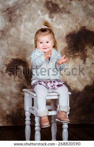 Adorable little girl with blond hair sitting on chair, laughing and clapping her hands. Studio portrait on brown grunge background - stock photo