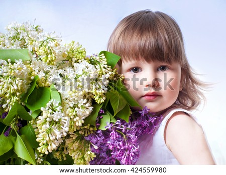 Adorable little girl with bouquet of lilac flowers
