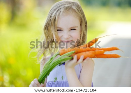 Adorable little girl with carrots in a garden - stock photo