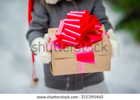 Adorable little girl with christmas box gift in winter day outdoors - stock photo