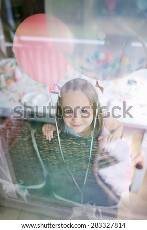 Adorable little girl with colorful balloons at kids birthday party looking through a window - stock photo