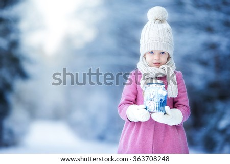 Adorable little girl with flashlight and candle in winter on Christmas outdoors - stock photo