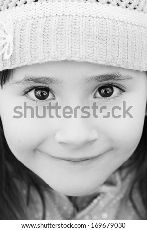 Adorable little girl with happy eyes closeup looking into the camera - stock photo