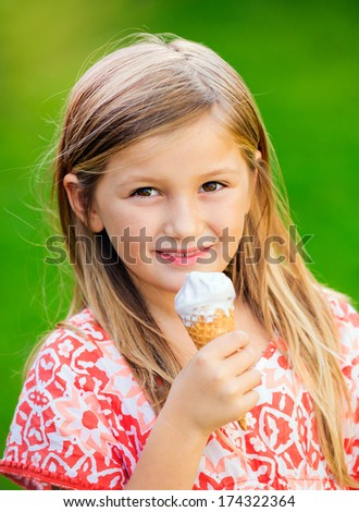 Adorable little girl with ice cream in the summertime - stock photo
