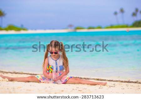 Adorable little girl with lollipop on tropical beach vacation