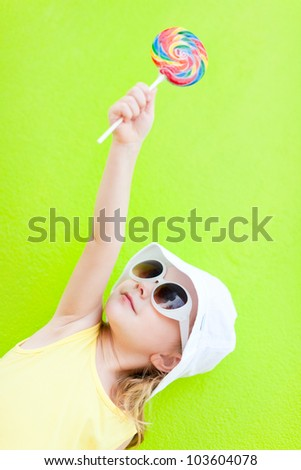 Adorable little girl with lollipop over colorful wall - stock photo