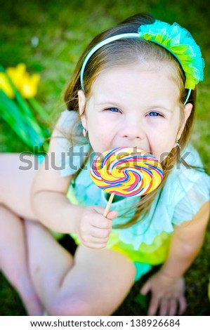 Adorable little girl with lollipop sitting on the grass - stock photo