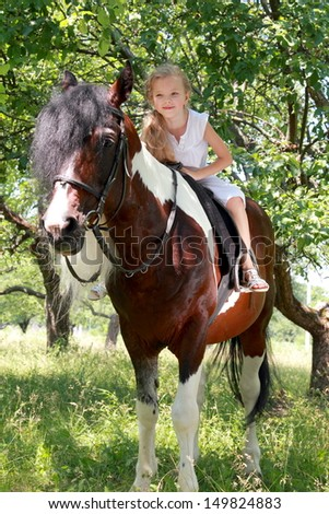 Adorable little girl with long hair and a sweet smile riding her pony