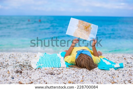 Adorable little girl with map find the way on tropical beach vacation - stock photo
