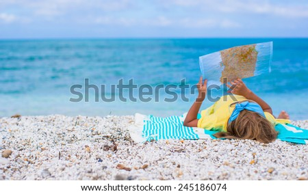 Adorable little girl with map of island on tropical beach - stock photo