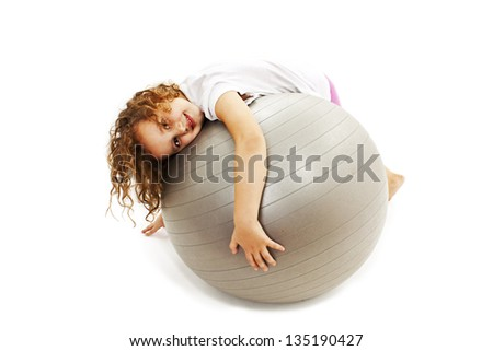 Adorable little girl with pilates ball. Isolated on white background