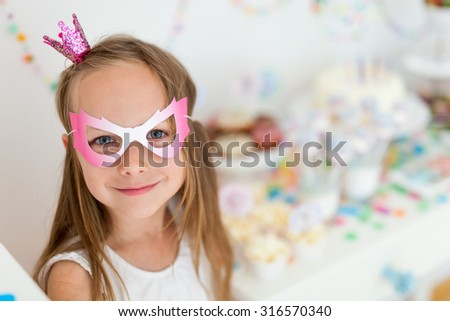 Adorable little girl with princess crown at kids birthday party - stock photo