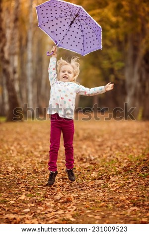 Adorable little girl with purple umbrella in the autumn park, jumping with umbrella