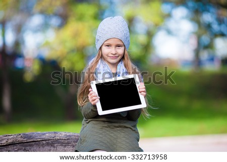 Adorable little girl with tablet PC outdoors in autumn sunny day - stock photo